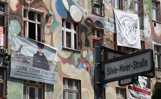 """Foto von einer Hausfassade in der Silvio-Meier-Straße mit """"Know-Your-Enemy""""-Transpi."""