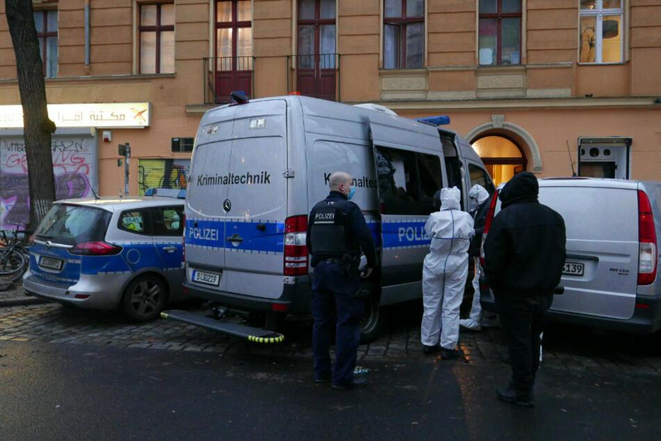 vor einem silber-blauen Transporter steht ein Cop im Einsatzanzug und 2 Personen in weißem Anzug der Spurensicherung