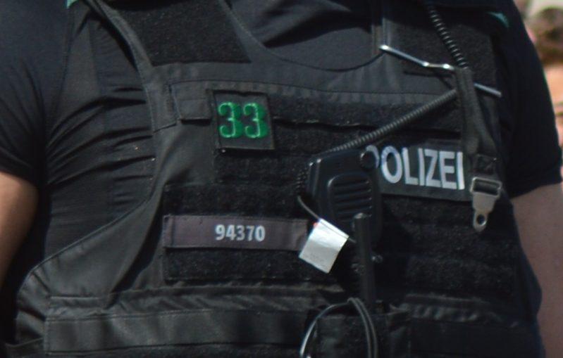 Bildausschnitt: Brustbereich eines Cops, der die Dienstnummer 94370 trägt