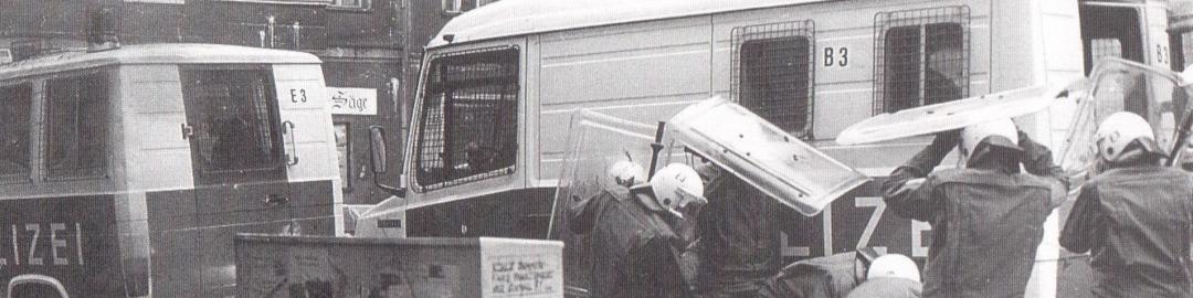 Ein Cop versteckt sich hinter einem Stromkasten vor Bewurf, dahinter schützen sich Cops durch Schilde und den GruKw.