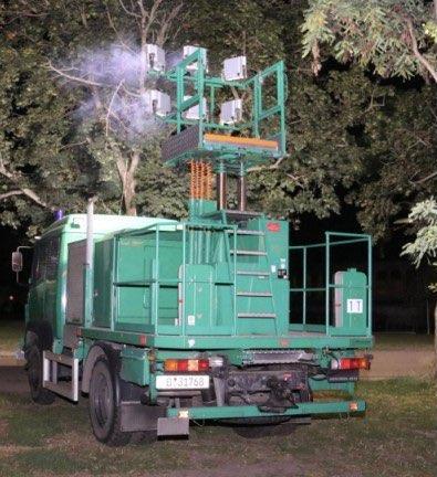 Grüner Lichtmastkraftwagen im Einsatz vor Baum.