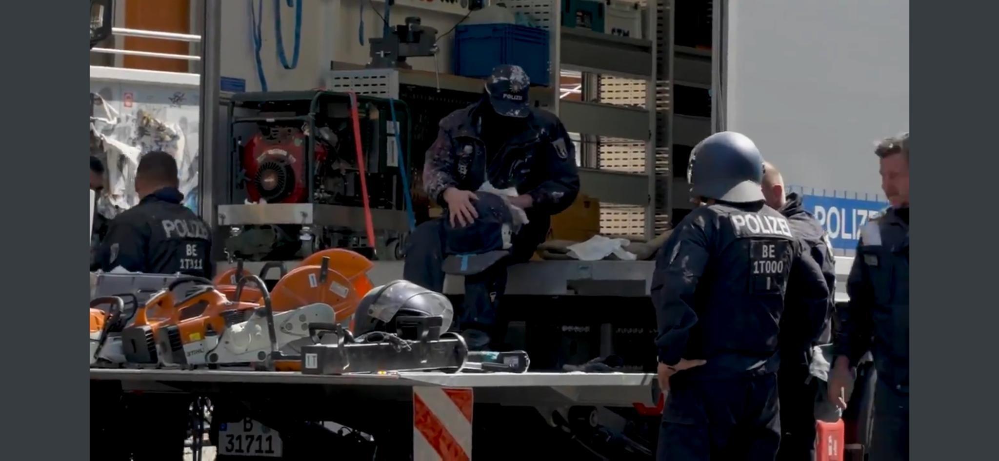 Blick in einen Laster mit Ausrüstung, mehrere Cops in Riot-Ausrüstung stehen davor