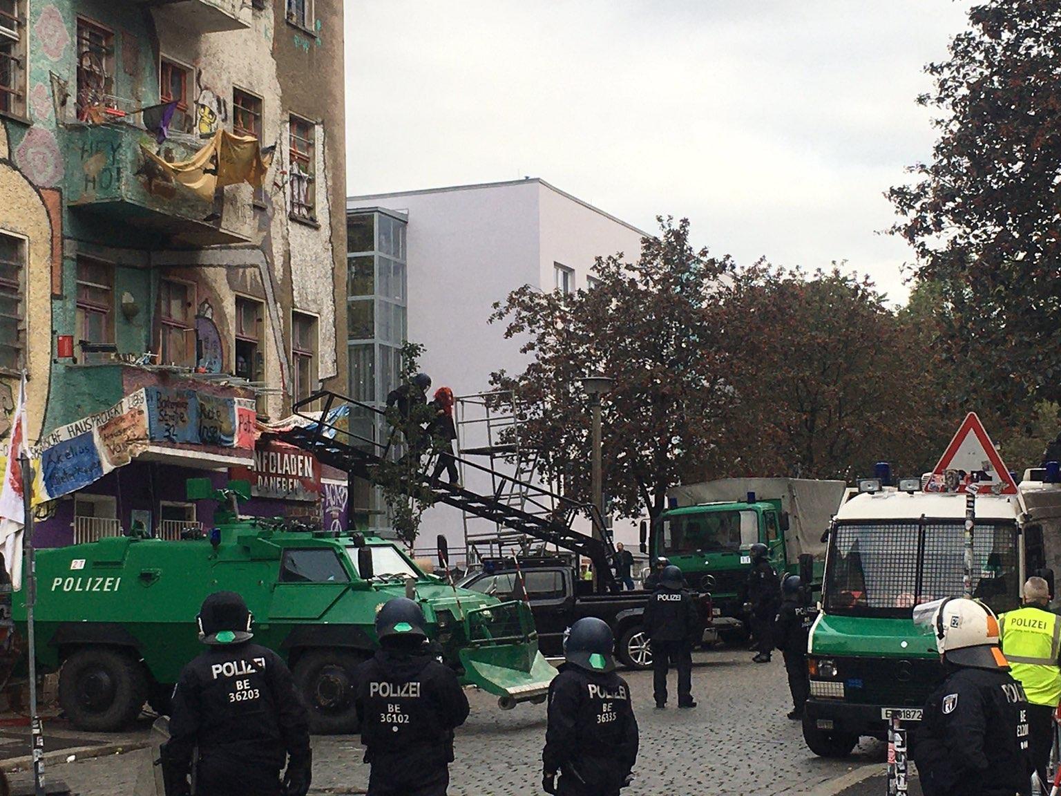 ein grünes Gefährt mit Treppe steht vor dem Haus. Cops versuchen über die Treppe zum Haus zu gelangen.