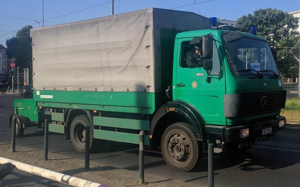 grüner Laster mit grauer Plane über dem Anhänger