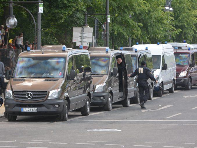 mehrer schwarze Mercedes-Transporter mit Blaulicht in einer Reihe am Straßenrand, aus dem zweiten von vorn steigen 2 Cops in schwarzem Einsatzanzug aus