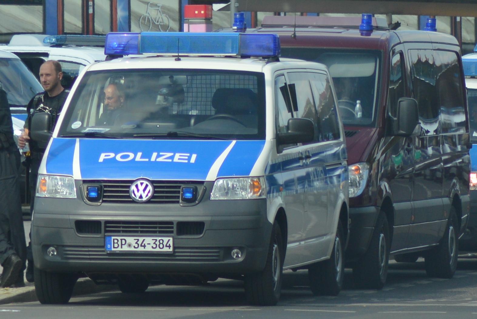 blau-weißer VW-Transporter mit Polizeischriftzug und Blaulicht