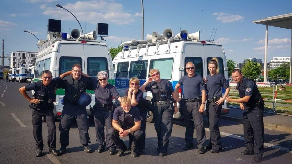 im Hintergrund sind 2 Lautsprecherkraftwagen in blau-weiß, vorn stehen 8 fröhliche Cops Arm in Arm