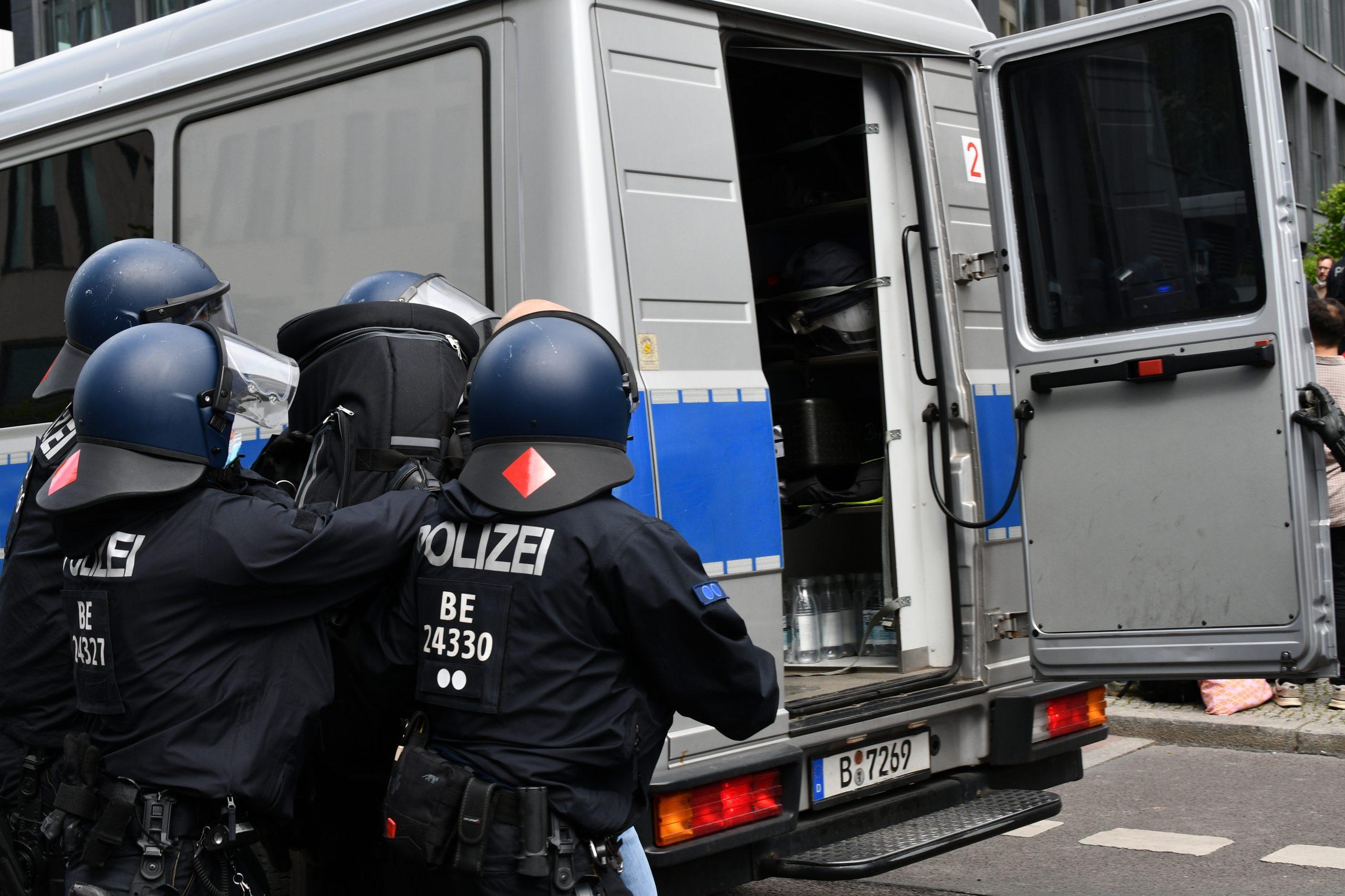 Ein silber-blauer Mercedes 813D von hinten, mehrere Cops in Riot-Ausrüstung stehen davor, die hintere Tür steht offen