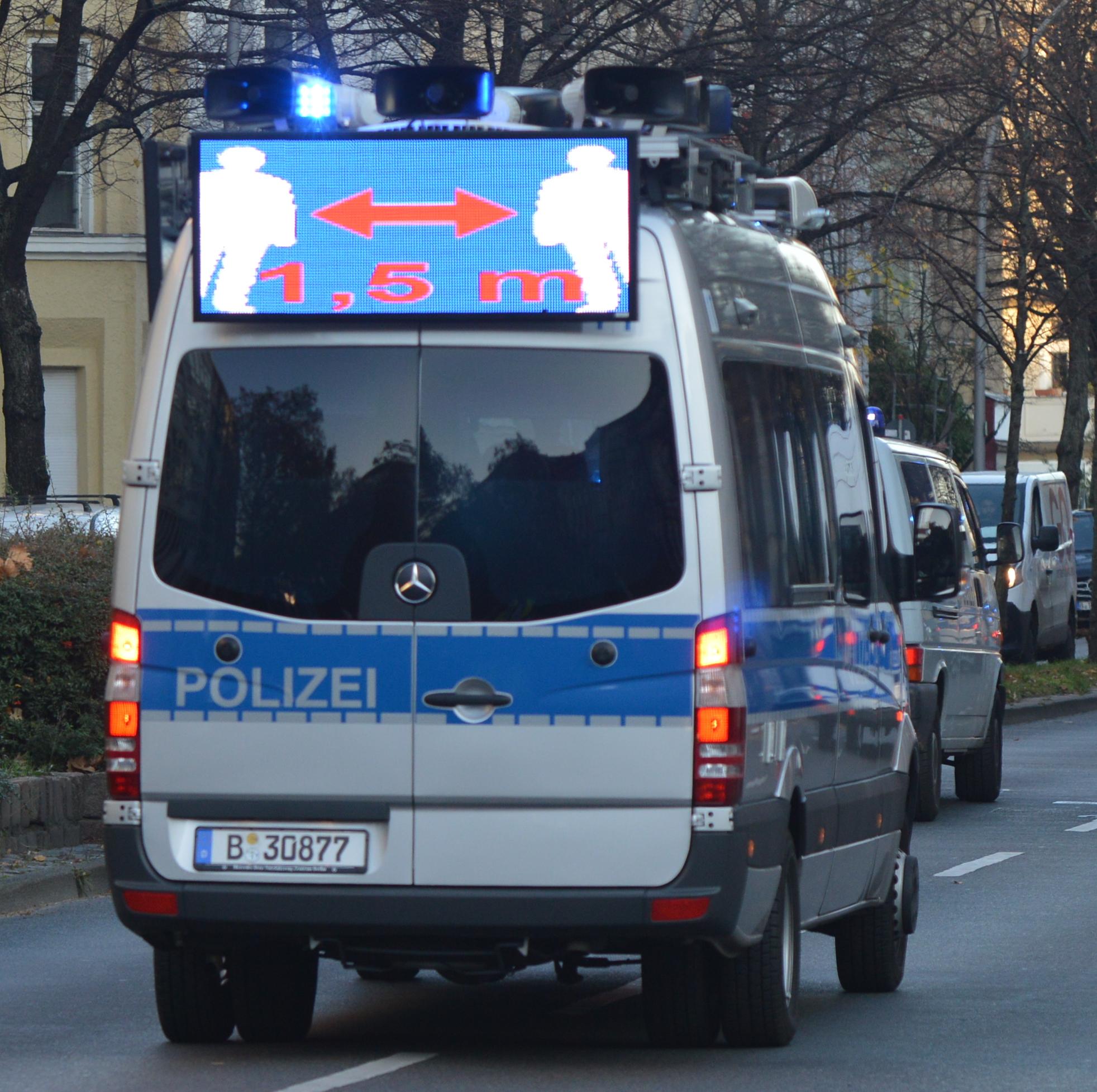 ein silber-blauer Lautsprecherwagen fährt auf der straße, man sieht ihn von hinten, am heck befestigt ist ein Bildschirm, der zeigt, dass 1,5 m Abstand gehalten werden muss