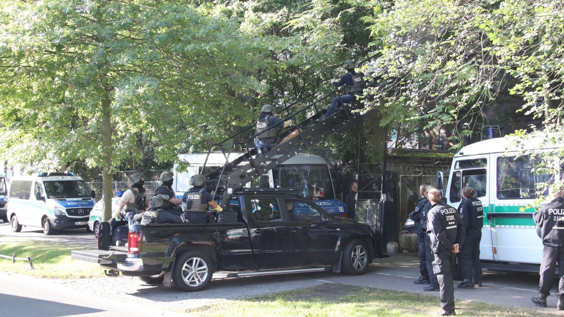 Man sieht einen schwarzen Jeep mit einer Treppe die zu einem Haus führt. Mehrere Cops sitzen auf dem Jeep, stehen drumherum, 2 Cops versuchen über die Treppe zu dem haus zu gelangen.