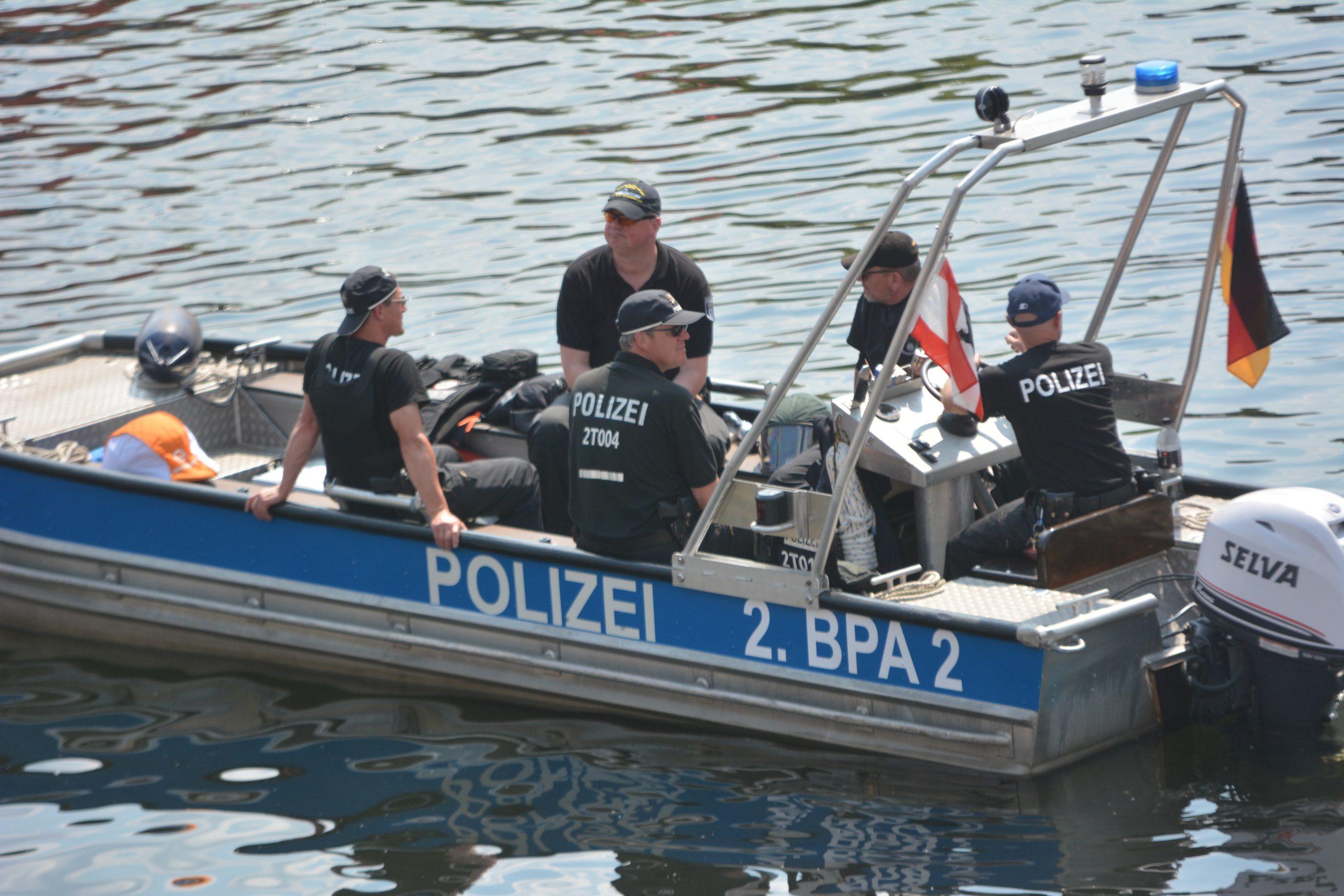 """kleines Motorboot mit 5 Cops drauf. es ist silber-blau, hat des Schriftzug """"Polizei 2. BPA 2"""