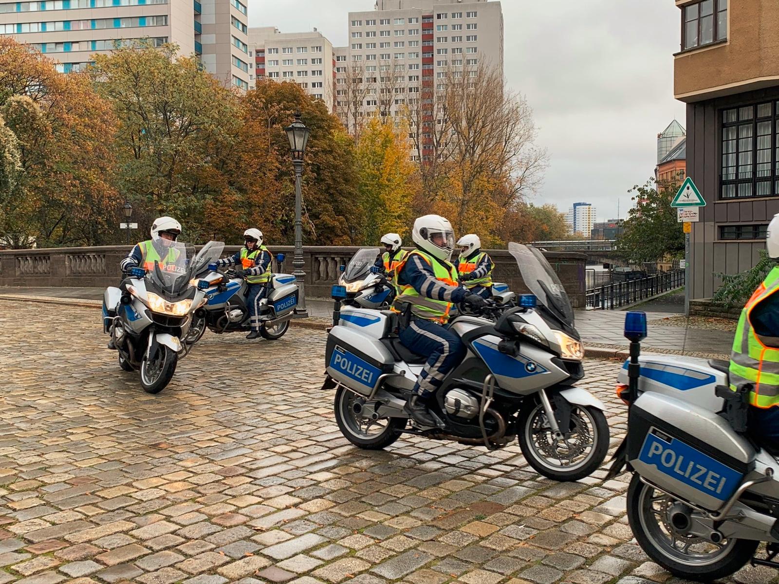Cops fahren mit blau-silbernen Motorrädern über Kopfsteinpflaster. Dabei tragen sie einen blauen Kraderlederanzug und Helm, sowie eine gelbe Warnweste.