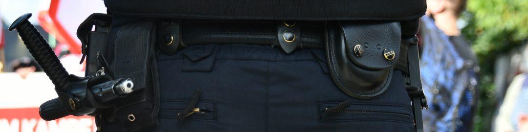 Hüfte eines Cops mit Tonfa und Dienstwaffe