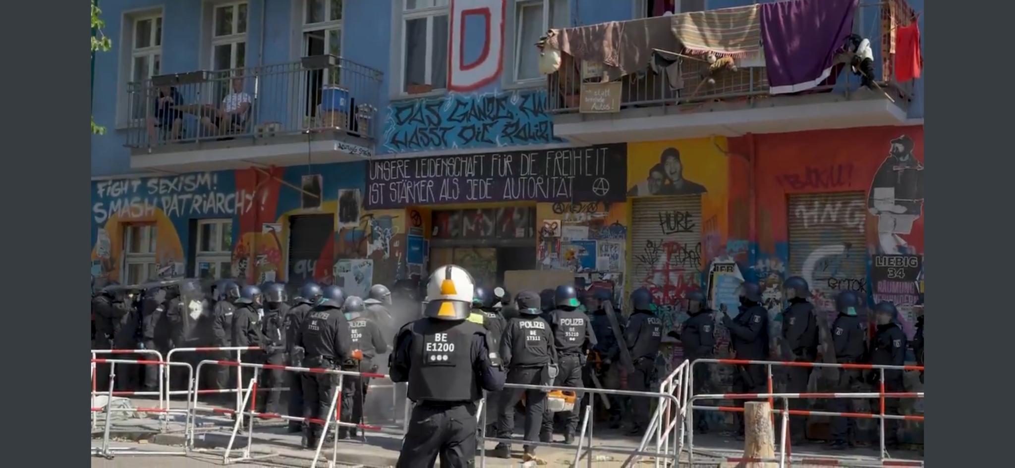 Cops versuchen in die Rigaer Straße hineinzugelangen. Dabei tragen sie Einsatzanzüge in dunkelblau und Helm. Die Fassade des Hauses ist bunt bemalt.