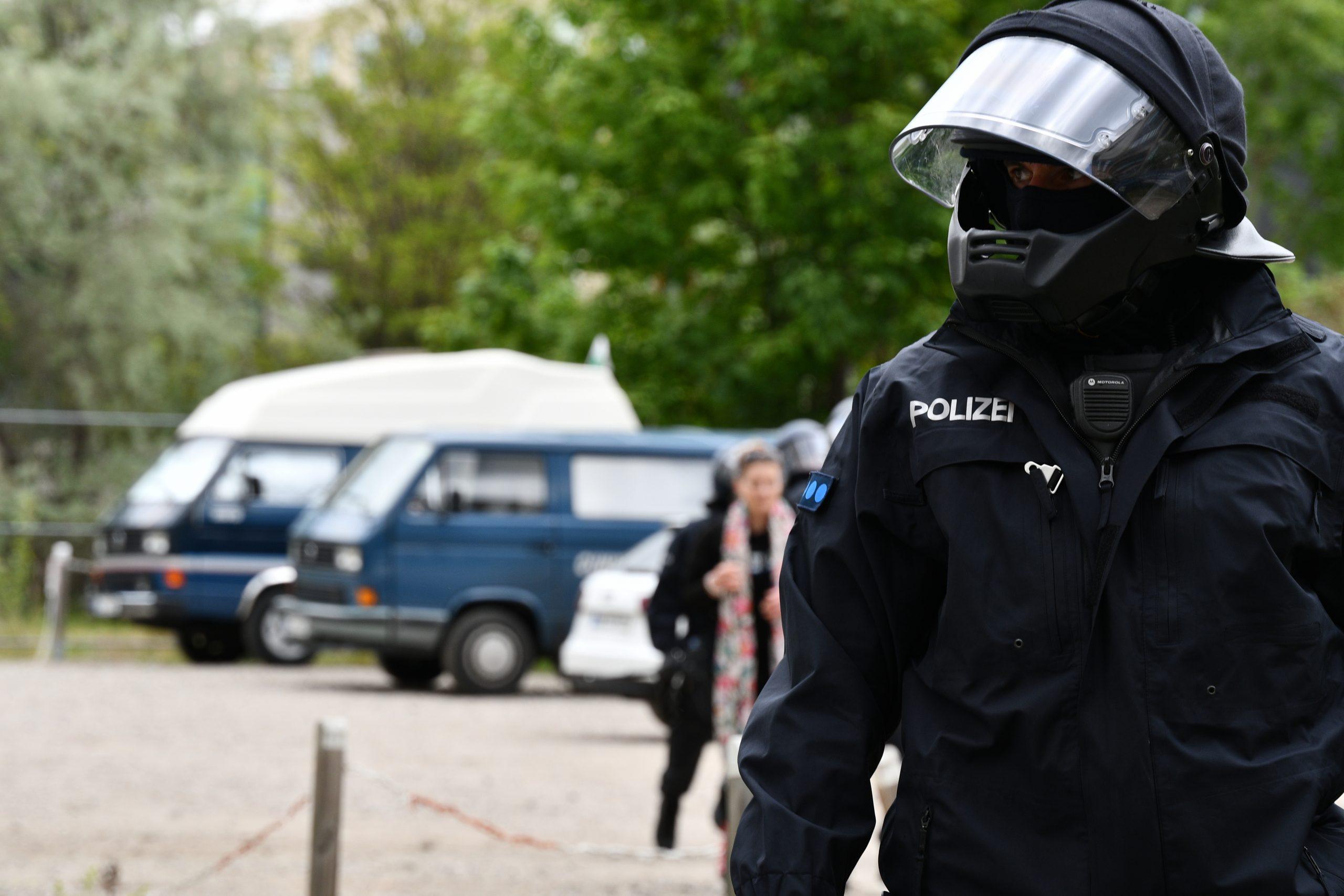 Oberkörper und Kopf eines Cops mit Helm und Einsatzanzug in dunkelblau. Am Helm ist ein Kinnschutz montiert.