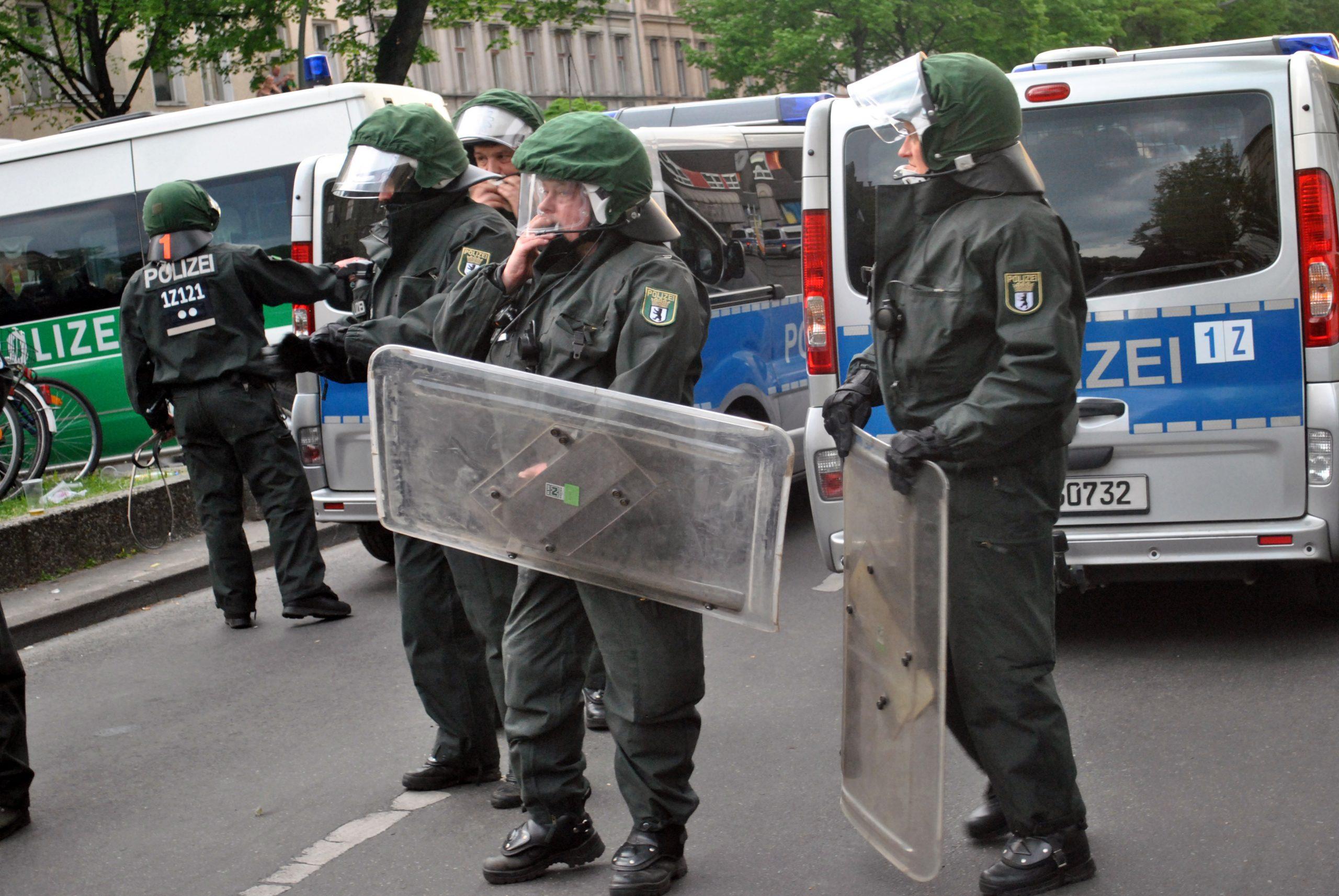 Mehrere Cops in noch grünem Einsatzanzug stehen mit Schilden auf der Straße.
