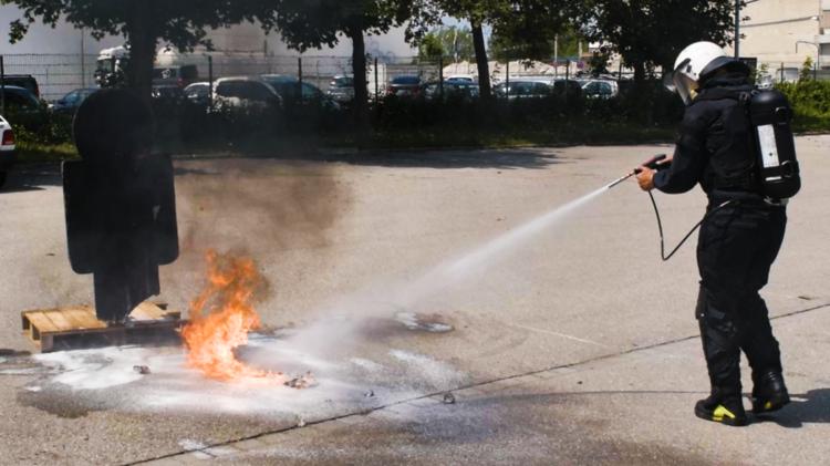 Person trägt einen Feuerlöscher in schwar auf dem Rücken und löscht einen kleinen Brand auf einem Parkplatz.