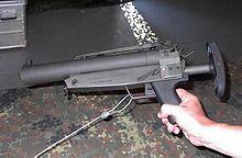 Eine MZP 1 liegt auf einer Camouflage-Decke. Sie hat vorne ein dickes Rohr aus dem die Granaten geschossen werden.