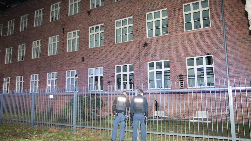 Die Backsteinmauern des BKA-Gebäudes sind mit schwarzen Farbgläsern beworfen worden. Davor stehen zwei traurige Polizisten.