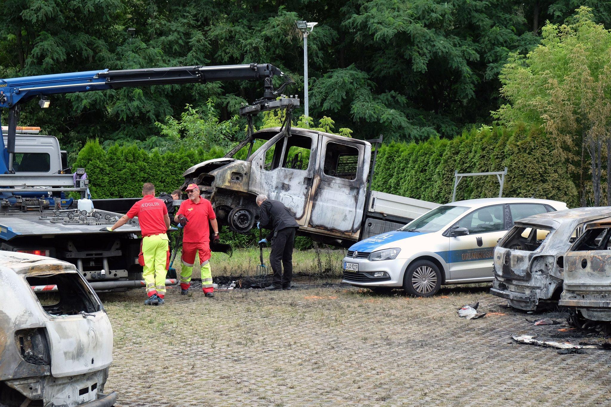 einige ausgebrannte Autos, eins wird von einem Kran hochgehoben