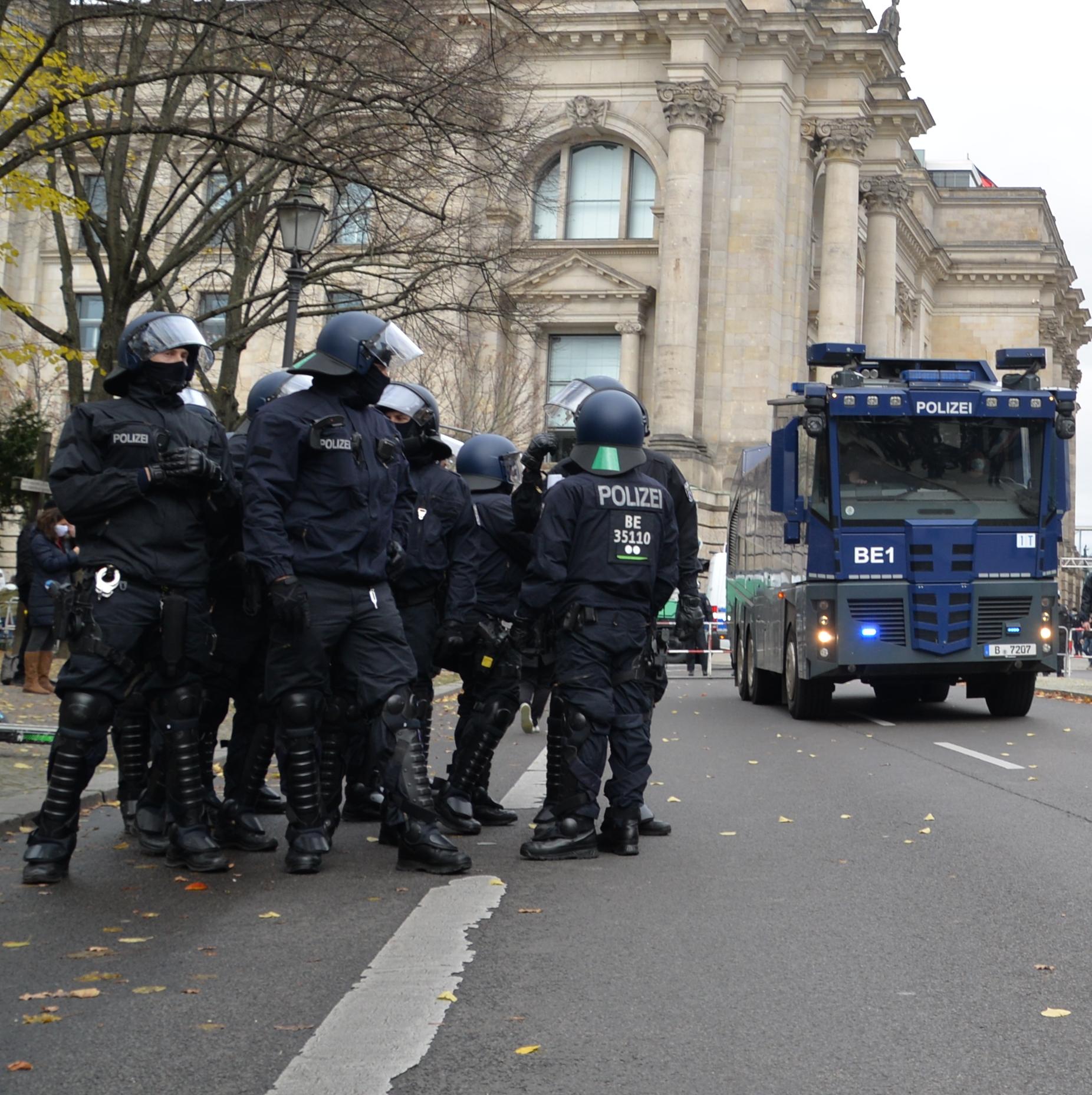 Ein Gruppe von Cops in Riot-Ausrüstung mit Knieschonern und Schienbeinschutz steht auf der Straße. Im Hintergrunf fährt ein blauer Wasserwerfer 10.