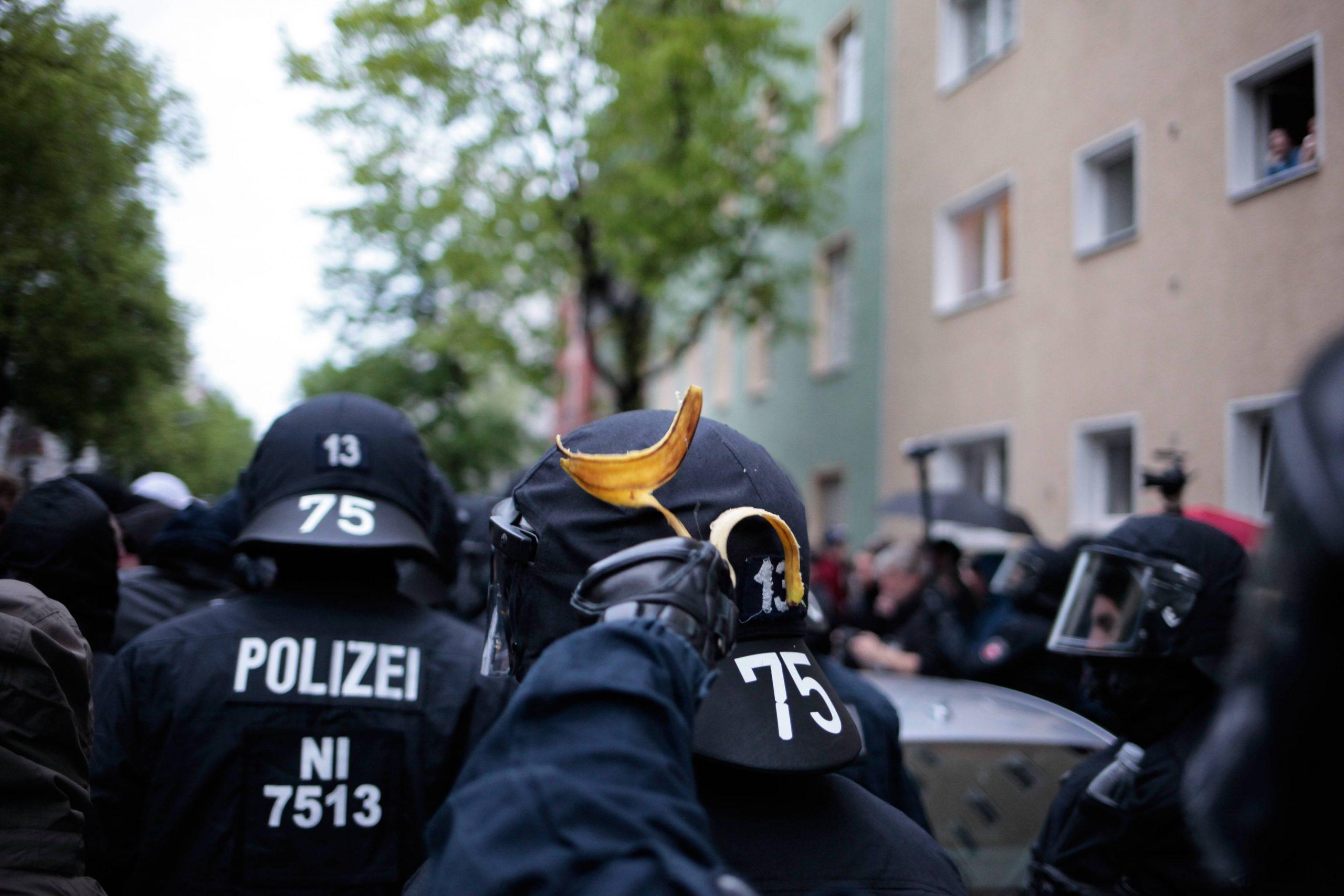 Auf dem Helm eines Bullen wurde eine Bananenschale geworfen, die von einem anderen Cop abgenommen wird.