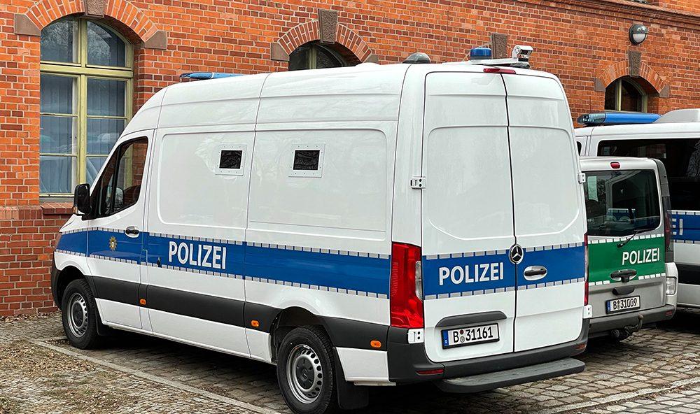 weißer Mercedes Sprinter mit blauem Polizeistreifen, von hinten