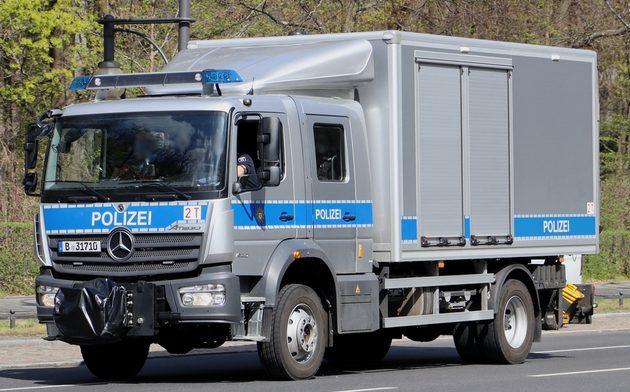 dunkelgrauer Mercedes Laster mit blauen Streifen