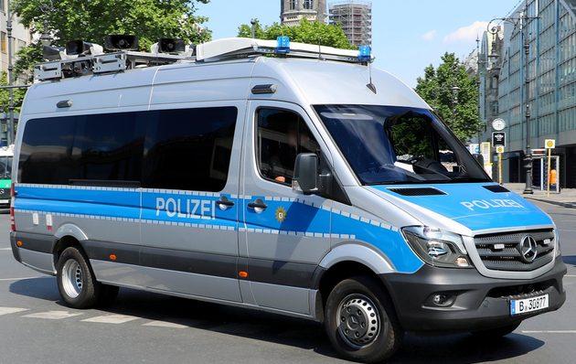 blau-silberner Mercedes-Sprinter mit Lautsprechern auf dem Dach