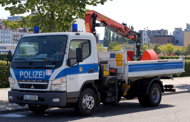 kleiner Laster in blau-weiß mit kleinen orangenen Kran hinten auf dem Anhänger