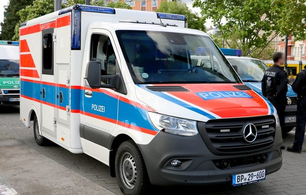 Sani-Fahrzeug von Mercedes in weiß mit orangenen und blauen Streifen und Polizei-Schriftzug