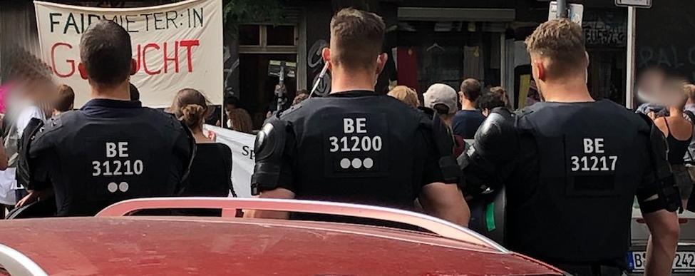 3 Cops von hinten mit taktischer Kennung, sie laufen hinter einer Gruppe Demonstrant*innen