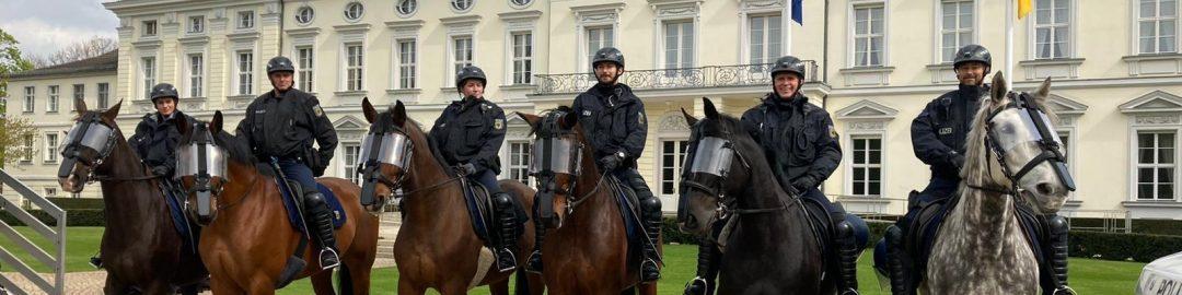 Aufgereihte Pferde plus Reiter:innen vor Bellevue.