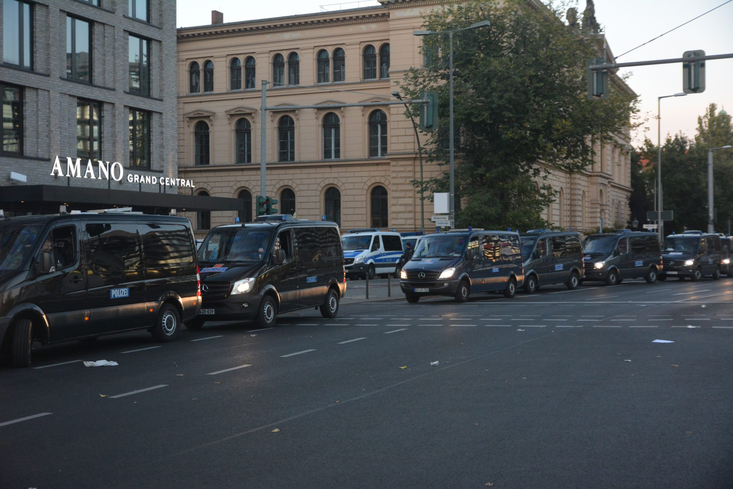 mehrere schwarze Mercedes Transporter mit Blaulicht und Polizei-Schriftzug am Straßenrand