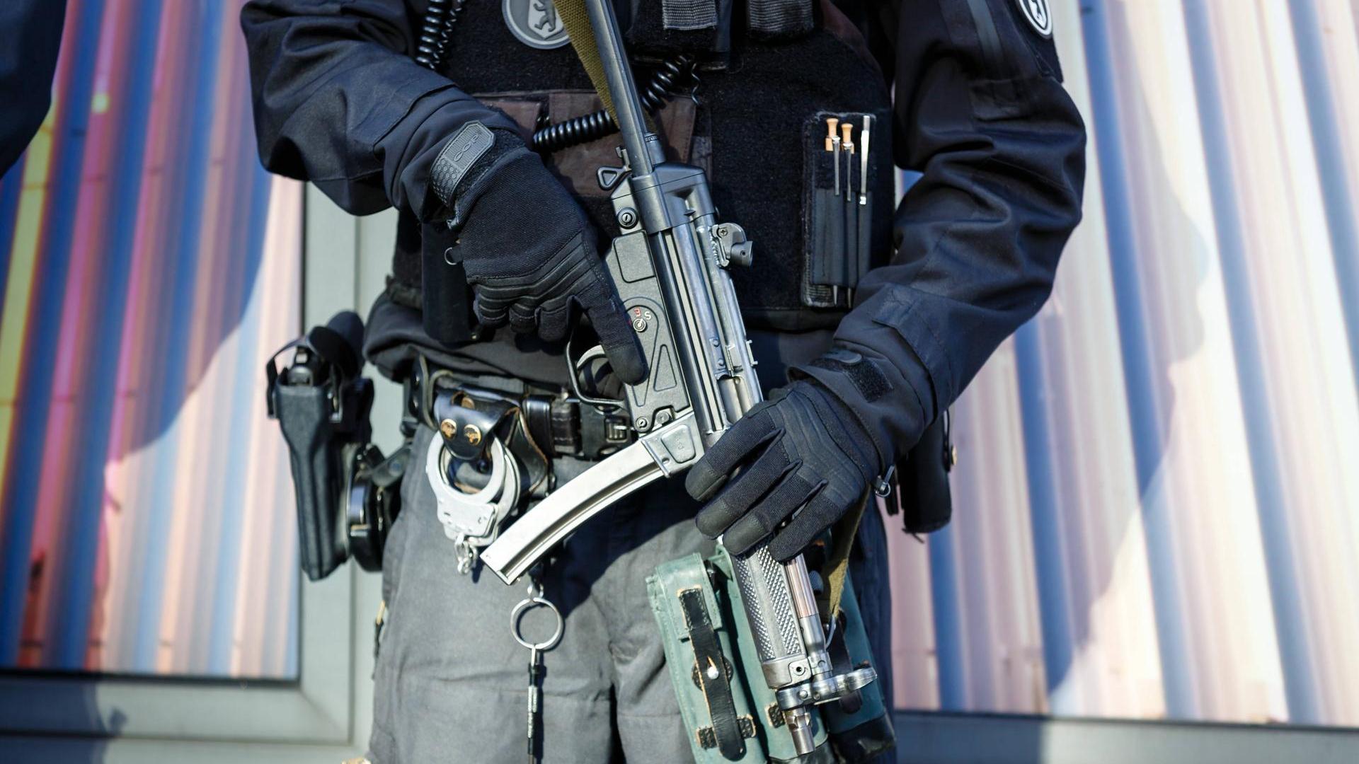 Oberkörper eines Bullen, der die MP5 in der Hand vor sich hält.