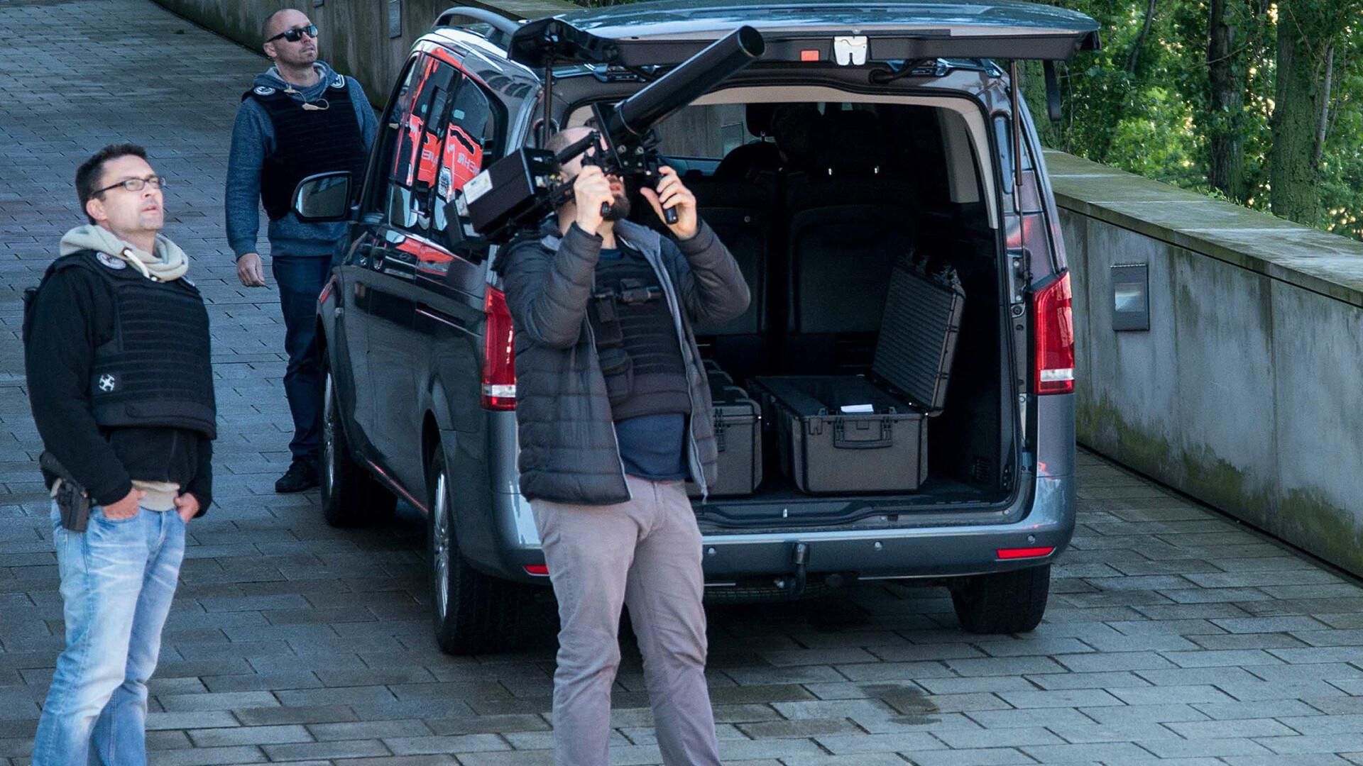 Drei Polizisten stehen vor einem Van. Einer zielt mit einer Art Waffe mit großem Rohr in den Himmel: Das Drohnenabwehrgerät HP 47.