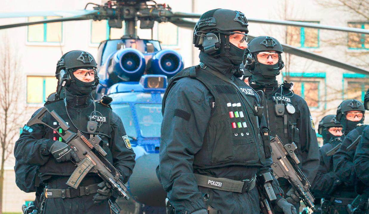 Mehrere Bundespolizisten vor einem blauen Hubschrauber. Die Cops tragen schwere Ausrüstung: Helm, Weste, Machinengewehre