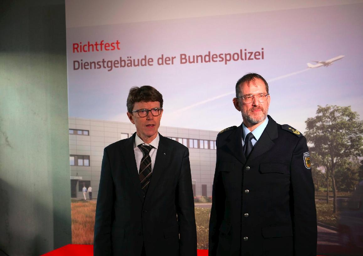 Zwei Männer vor einem Plakat mit dem Foto des neues Bundespolizeigebäudes. Links ein mittelalter Mann im Anzug: Engelbert Lütke Daldrup. Rechts ein mittelalter Anzug in Polizeiuniform der Bundespolizei: Karl-Heinz Weidner.